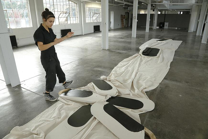 Artist arranging her piece of white cloth with black and white oblong shapes in the middle.