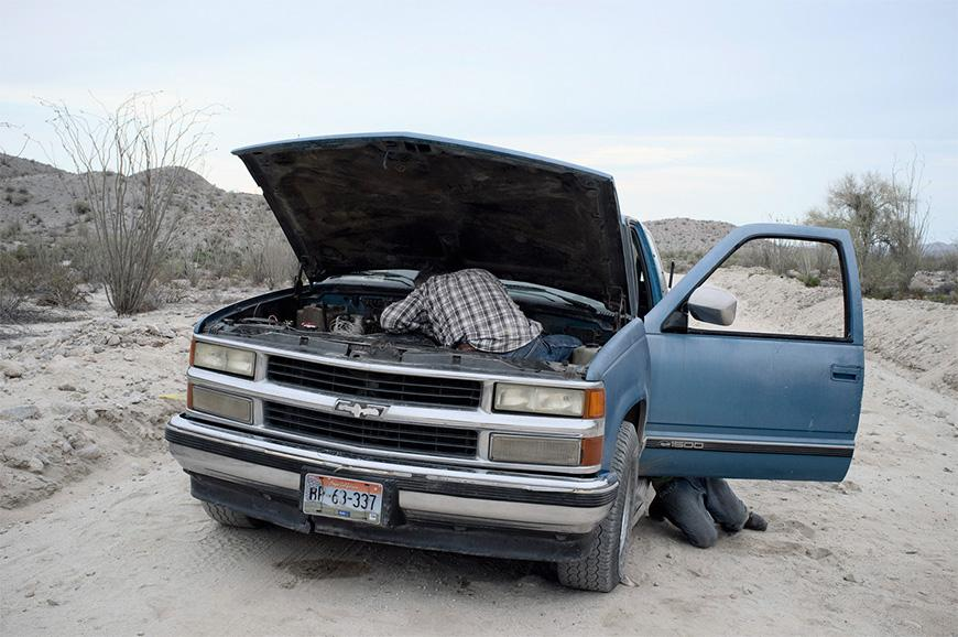 Blue vehicle with hood popped up and a person wearing a checkered shirt working inside hood, driver side door open with someone kneeling behind door in the middle of a desert.