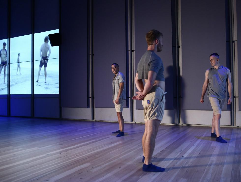 Three people standing in a triangle wearing gray shirts and light shorts with a projector in the left with people standing similarly.