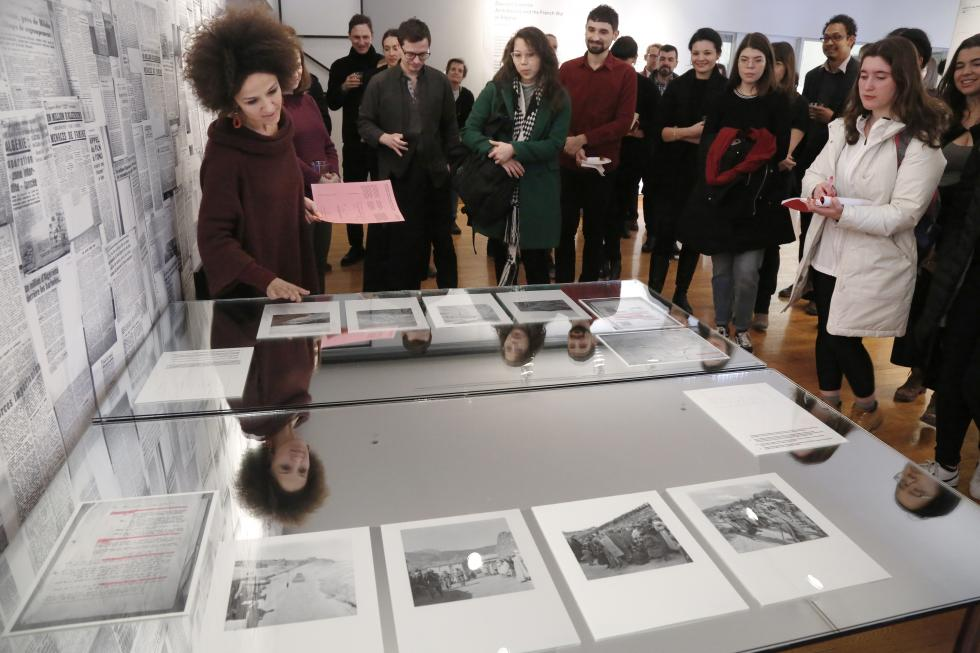 A woman points to a discplay of documents in front of a group of students
