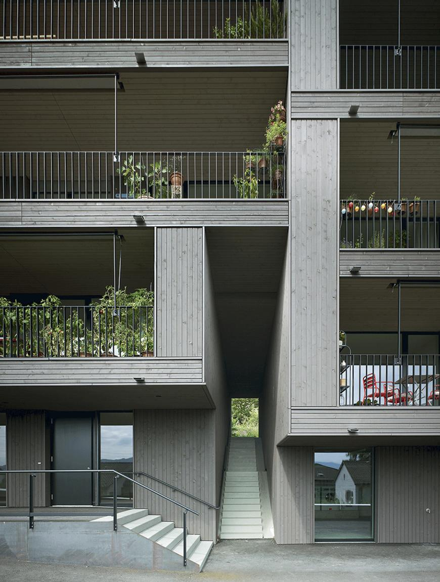 a gray woodent apartment building facade with stairs and balconies