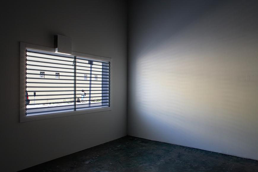 Corner of a room with a window with blinds open letting in light into a dark room.