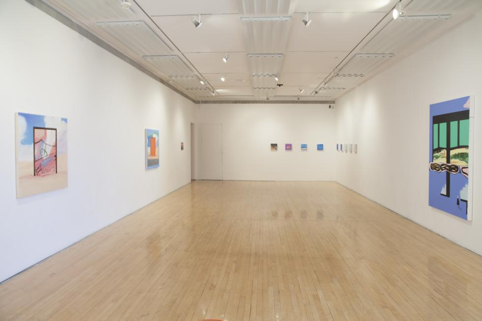 Installation view of paintings exhibited in a long white room with wooden floors.