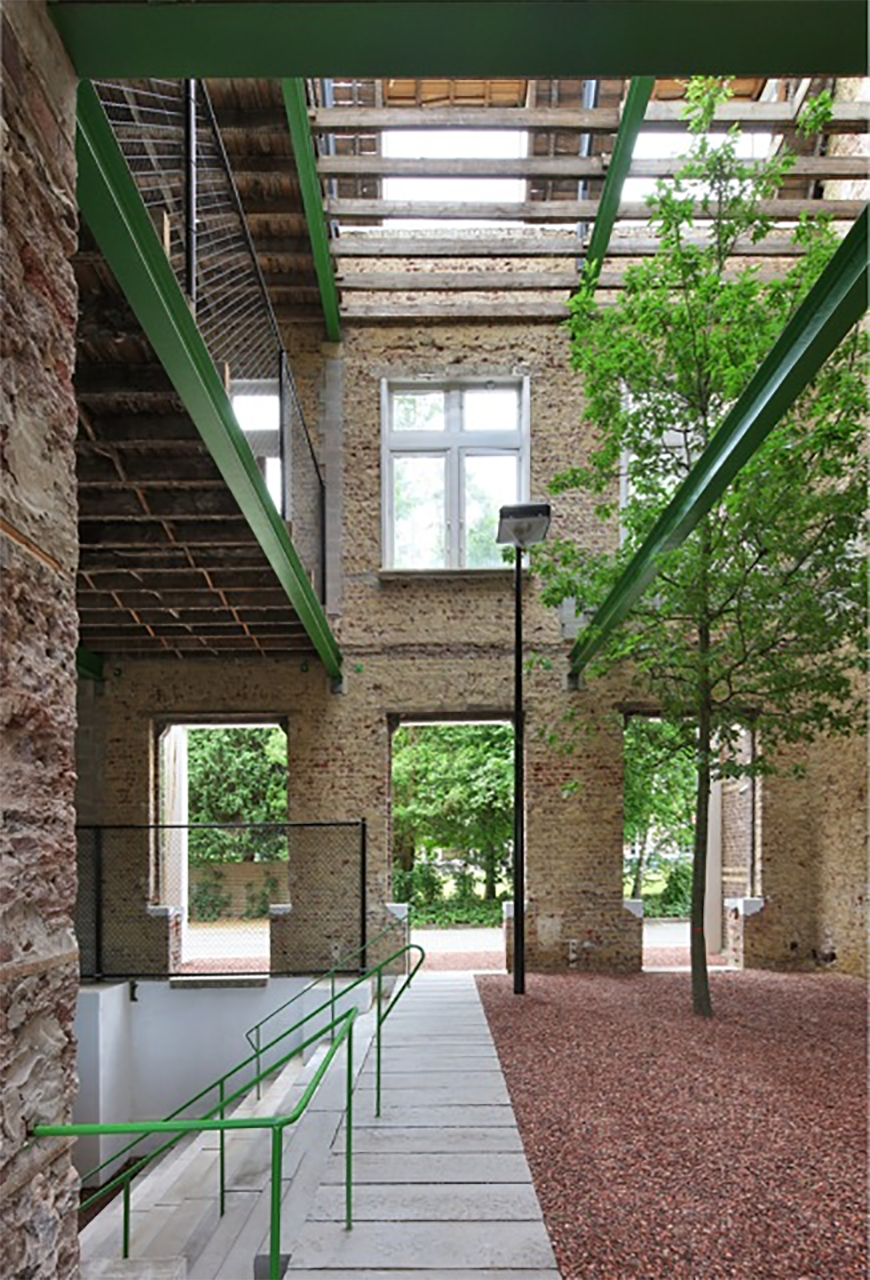 Inside a building whose interior has been removed, and opened to the outdoors.