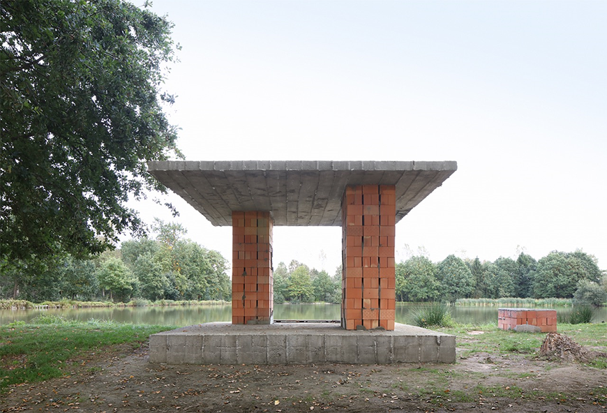 A small, minimal pavilion constructed from cement and two brick pillars. The pavilion is situated next to a pond.