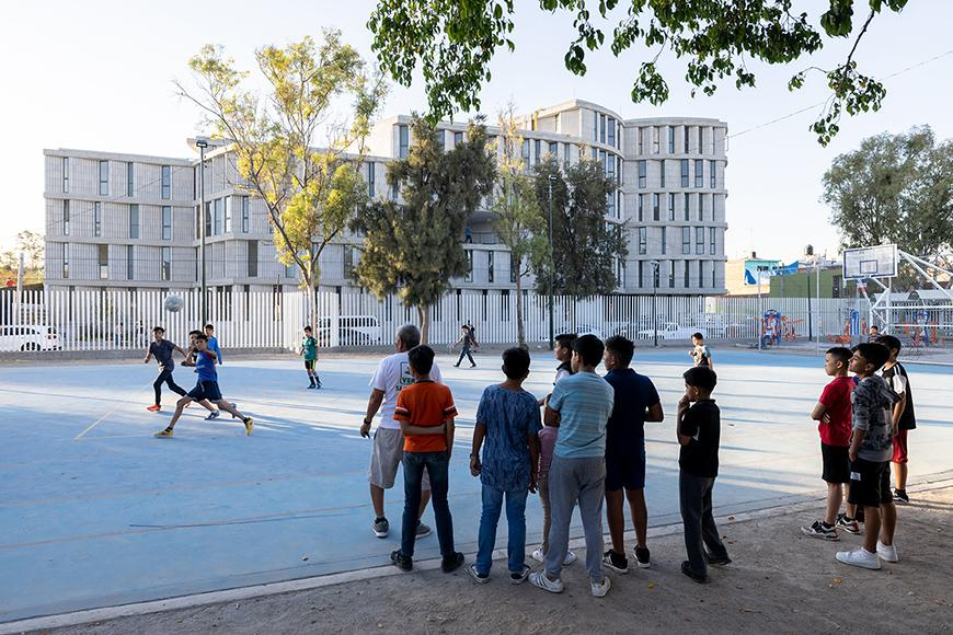 Childredn playing sports on a playground, apartment-style building in background.