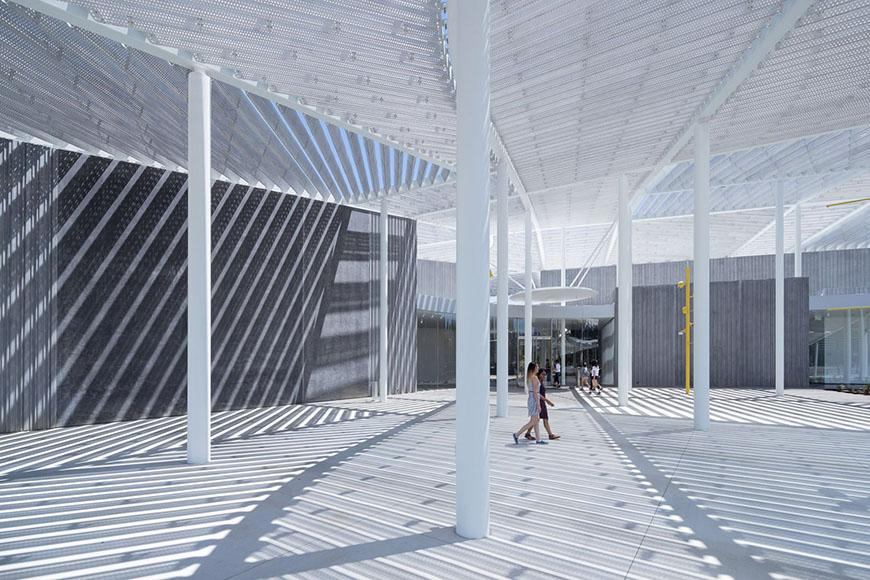 A white courtyard awning structure casting shadows on the ground.