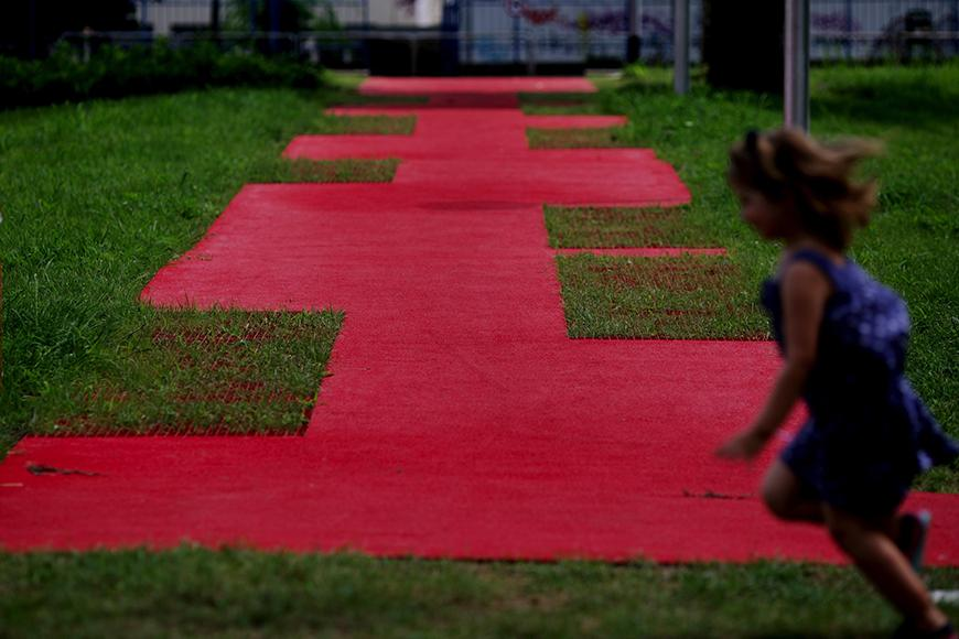 girl running in front of a red mat over a grassy area