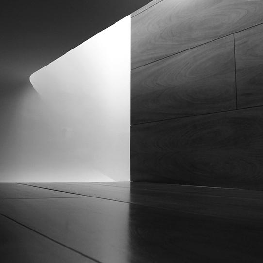 A black and white photo of a curved wall and floor