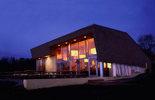 Evening view of house with interior lit.
