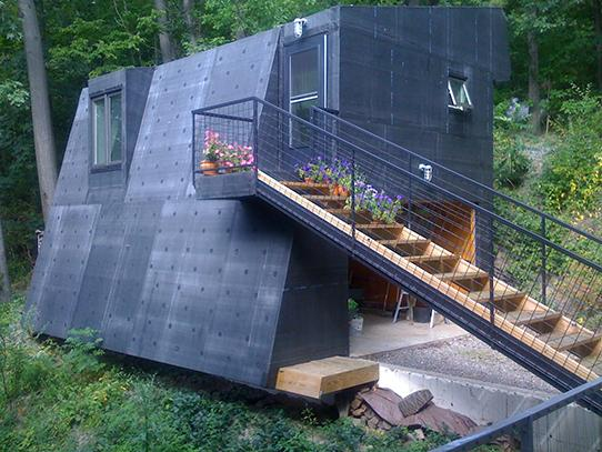 a dark colored metal clad contemporary tiny house with an angled wall and set of stairs on the outside