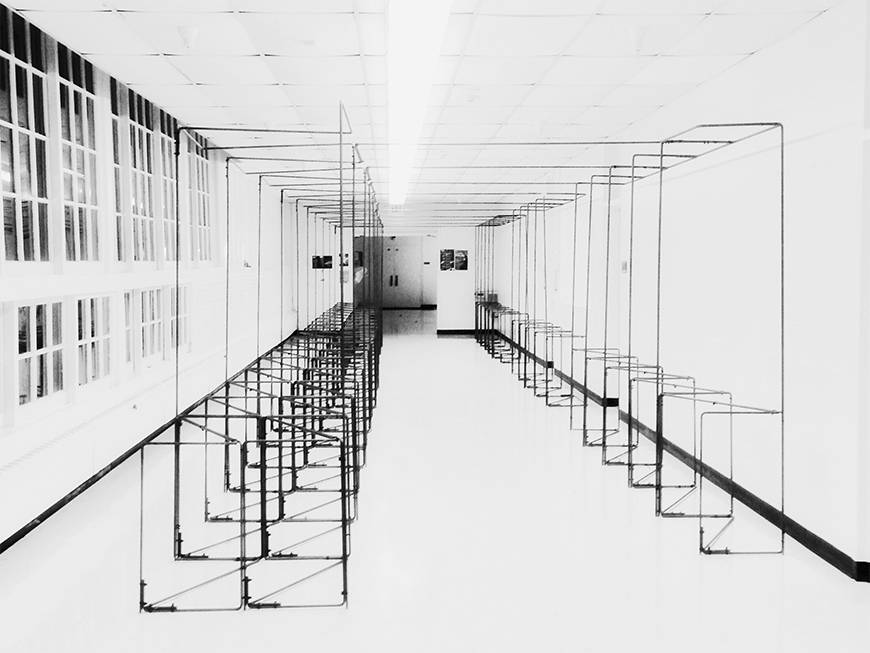 Black and white photograph situated at the end of a long hallway, which is occupied by a series of demountable self-supporting display systems constructed from steel rods.