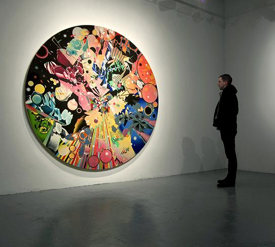 a vibrant abstract multimedia artwork in the shape of a circle haging in a gallery with a man looking on