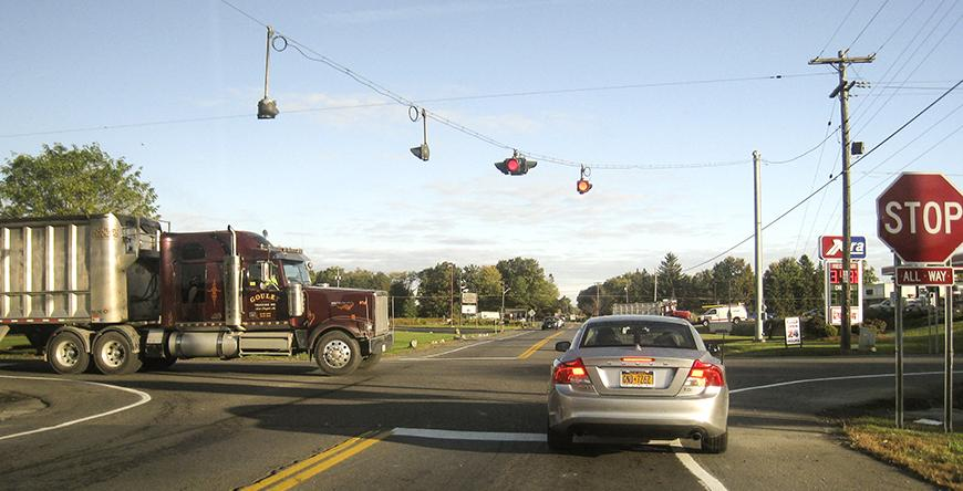 Photograph showing a truck and a car at a Lansing intersection