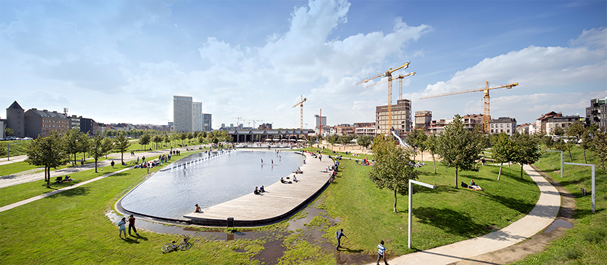 Landscape of a park centered around an artificial pond within a cityscape.