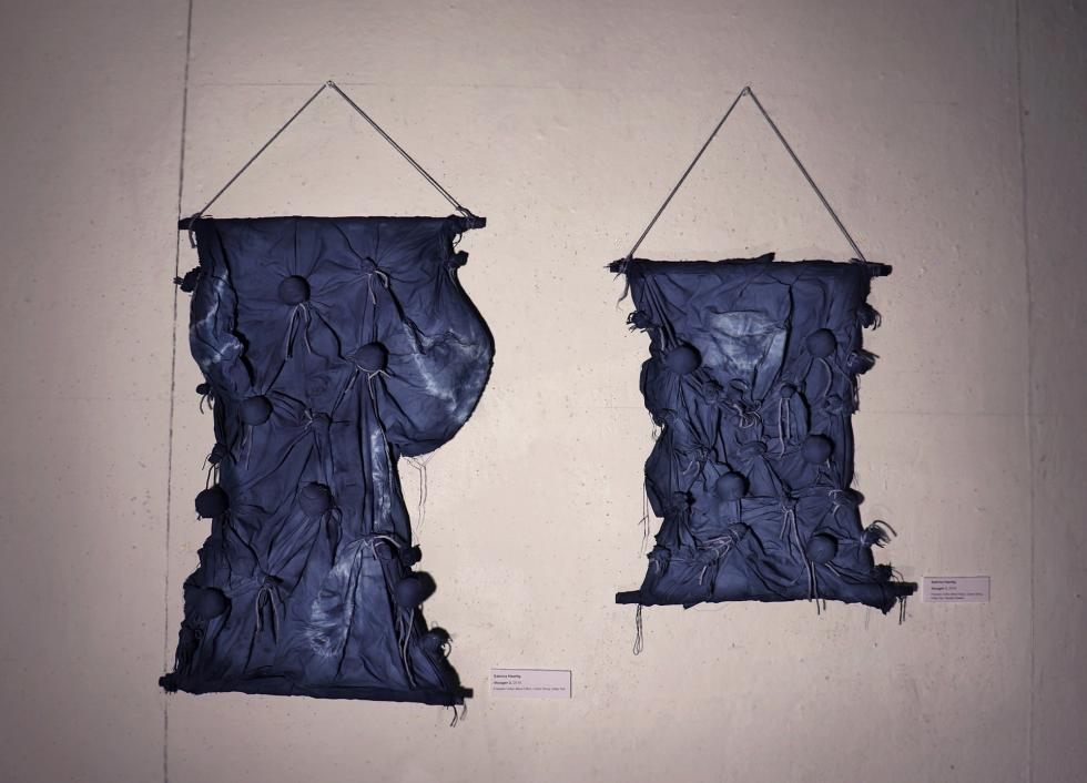 Two pieces of dark purple fabric with bunched up pieces hung from the wall.
