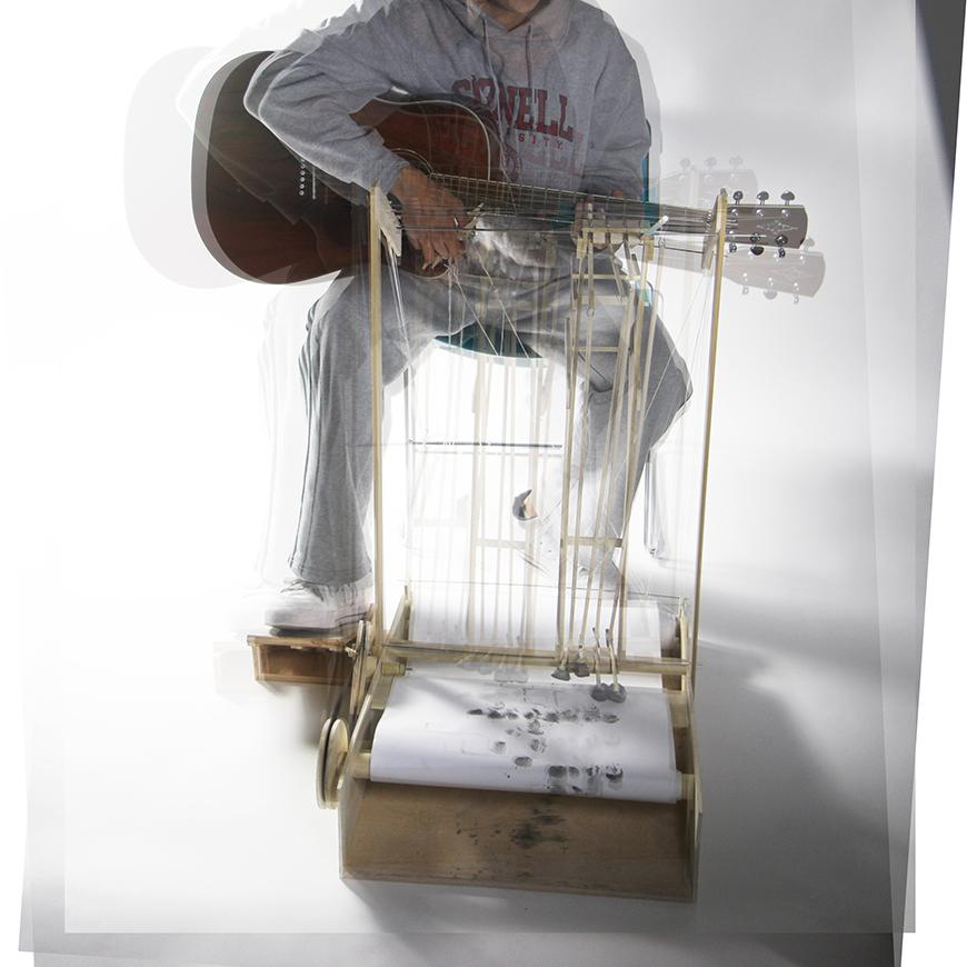 Time lapse photograph of a drawing machine propelled by a guitar.