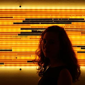 shadow portrait of a person in front of a orange black striped screen