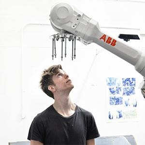 a young man in a black t-shirt looks up at a robotic arm above his head