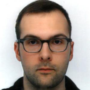 headshot of a man with dark hair and glasses