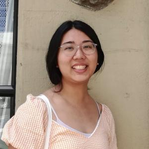 Girl with dark hair loosely pulled back wearing a light orange striped shirt against a pale tan wall.