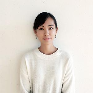 head and torso of a young woman with black hair wearing a white sweater standing against a white wall