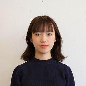 A young woman with shoulder length brown hair and bangs, wearing a long sleeve black shirt.