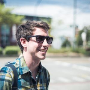 headshot of a young man in a plaid shirt wearing sunglasses with a street behind him