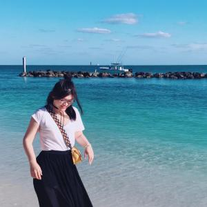 woman walking on a beach wearing a white shirt and black skirt with blue ocean and sky behind her