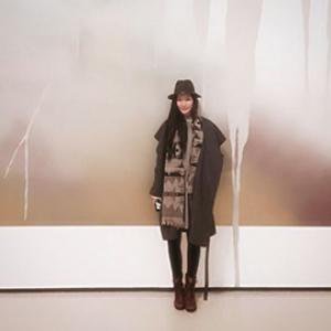 portrait of a woman from a distance wearing a hat standing in front of a brown and white wall