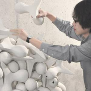 person adding white sculpture to a pile of similar sculptures