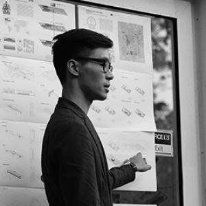 profile of the torso and head of a young man with dark and glasses standing in front of a diagram