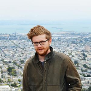 head and torso of a man with reddish hair and glasses with a cityscape behind him
