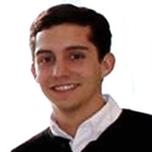 young man with dark hair wearing a white collared shirt and dark sweater