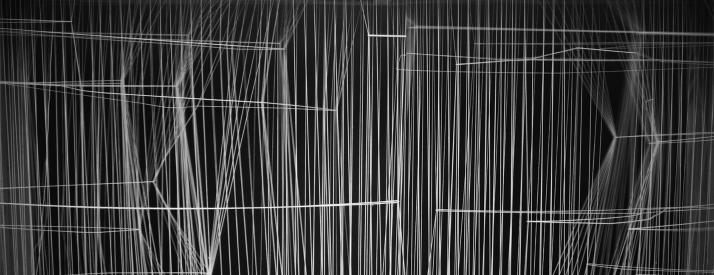 Photograph on black background of model made of thin white strings held in tension to create varying densities, translucency, and shapes.