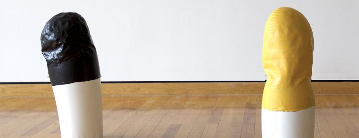 Two abstract sculpture objects, one with a black top half, and one with a yellow top half, both with white bottoms, set on a wooden floor against white wall.