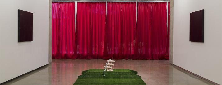 Two white walls with identical dark canvases facing each other, red curtains in the background and a tan abstract sculpture piece on green turf.