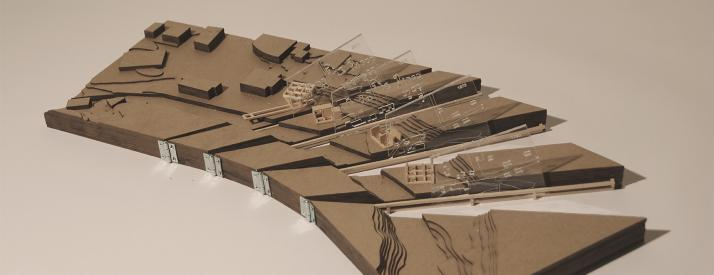 Photograph of model made of chipboard and basswood, sliced into sections connected to each other by hinges with laser-cut plexiglass separating each section.