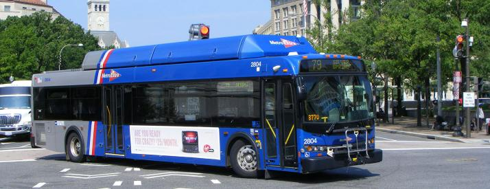 a blue city bus making a turn on a road