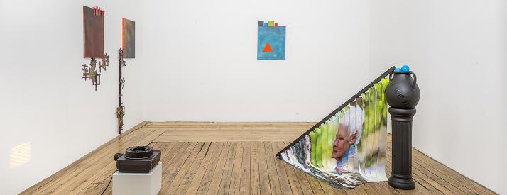 Small slide show projector, three paintings on the wall in various hues of orange and blue with Popsicle sticks and a black pedestal with vertical blinds draped towards the floor with Judi Dench's face.