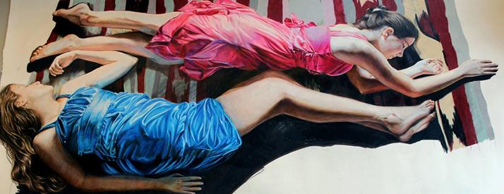 A drawing of two girls laying on a grey and red striped background wearing pink and blue dresses.