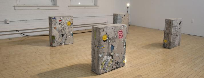 Cinder block sculpture pieces with random objects stuck inside.