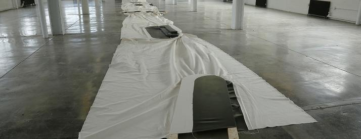 long white cloth with a black oblong wooden shape in certain parts of it.