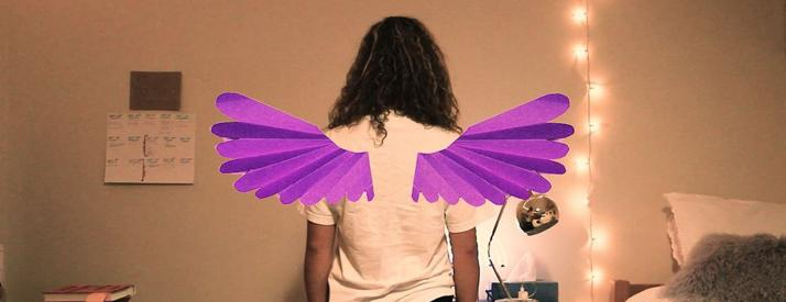 Image of a student's back facing the camera wearing purple colored construction paper wings.