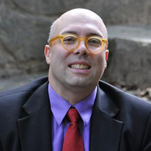 bald man wearing orange glasses a purple shirt and a red tie