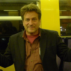 A man with unruly hair wearing a brown checked shirt and black jacket
